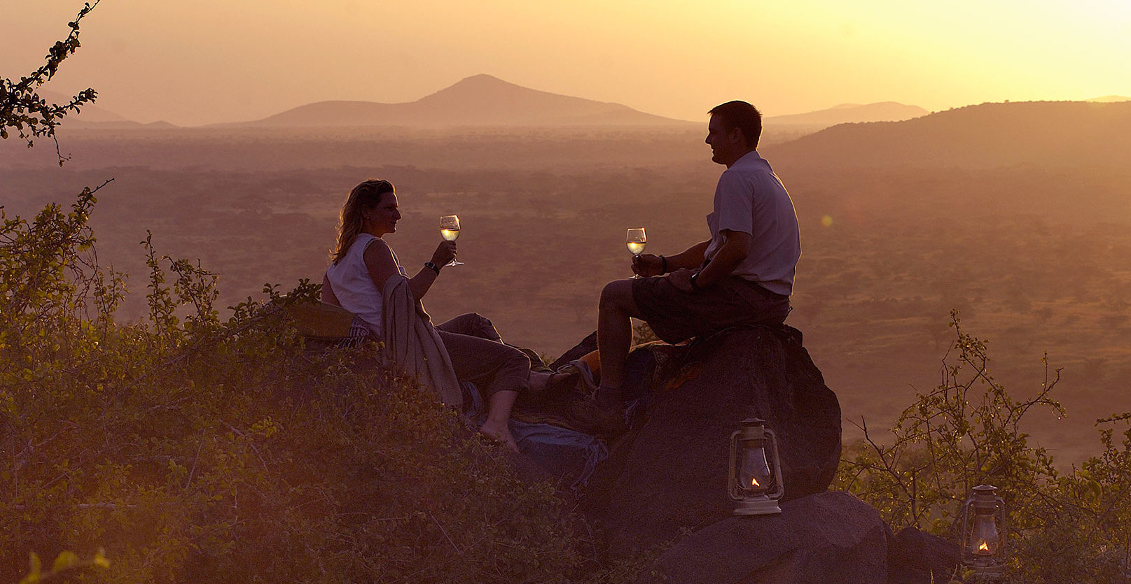 A couple toasting to a blissful marriage while taking in the magnificent view of the African landscape on their African safari honeymoon.
