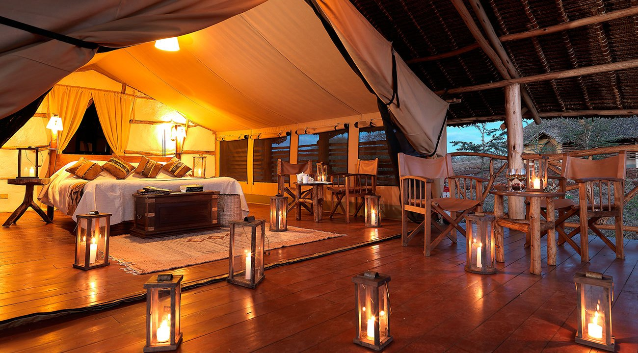 Several lighted candles casting a soft glow in a spacious, nicely decorated African safari honeymoon suite.
